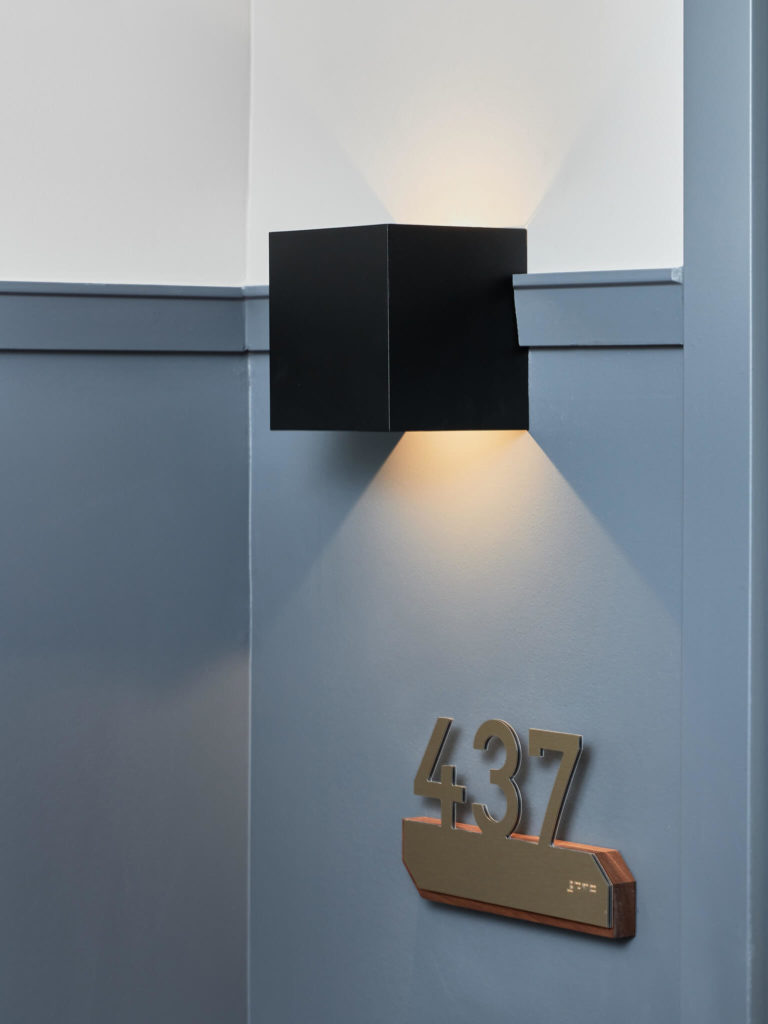 Apartment door with black wall light and number plate